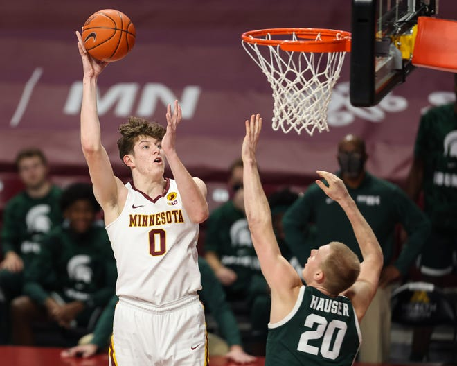 Liam Robbins (0) from Minnesota Jover hits Michigan state striker Joy Hauser (20) on December 28, 2020, during the first half at the Williams Arena.