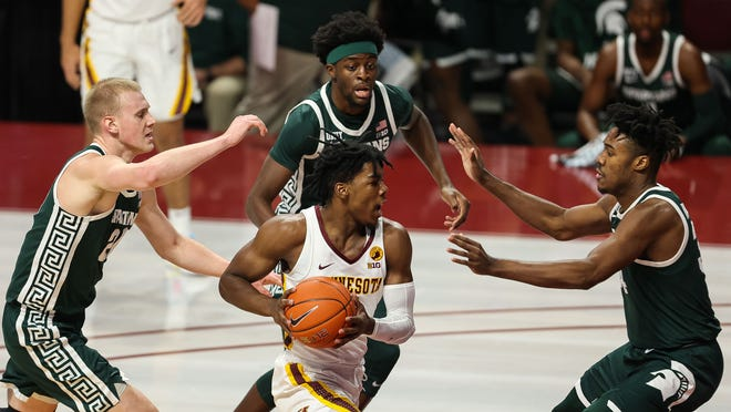 December 28, 2020;  Minneapolis, Minnesota, USA;  Marcus Carr leads Minnesota goalkeeper Jover (5) to the basket as Michigan State Spartans guard him during first half at the Williams Arena.  Mandatory credit: Harrison Barden-USA TODAY Sports