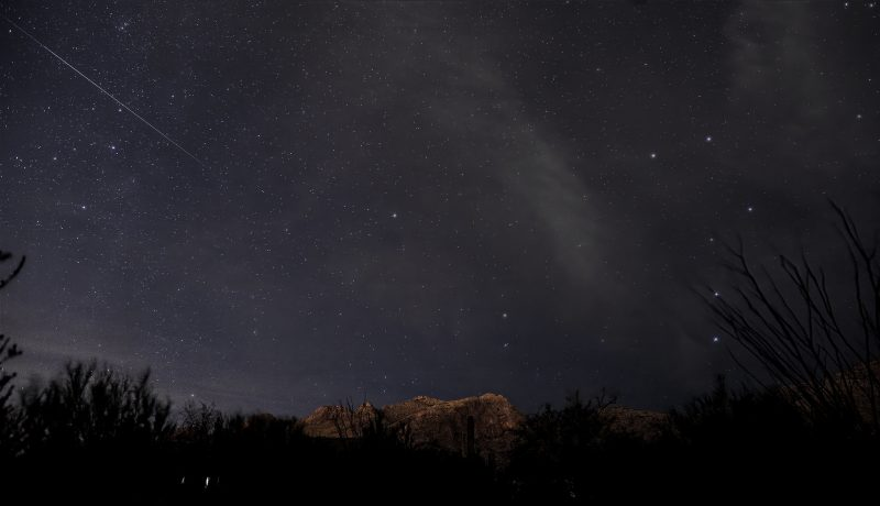 A thin, bright streak in a dark sky, with the Big Dipper visible.