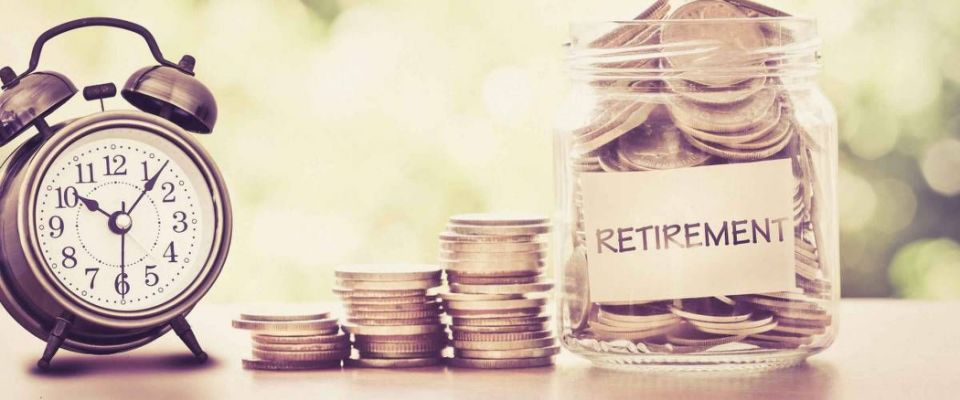 Putting coins in glass jar with old alarm clock to save time to save money for retirement concept, vintage color tone