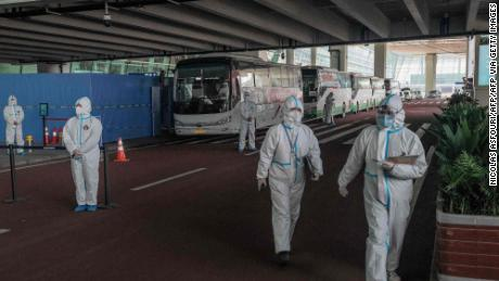 Health workers stand next to buses in a closed section, where incoming travelers will be transferred to quarantine, at the international airport in Wuhan, China, on January 14, 2021, after the arrival of an investigation team of the World Health Organization (WHO).  The origins of the COVID-19 pandemic.